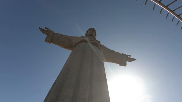 vídeos de stock e filmes b-roll de low angle view of jesus christ statue in lisbon - monumento