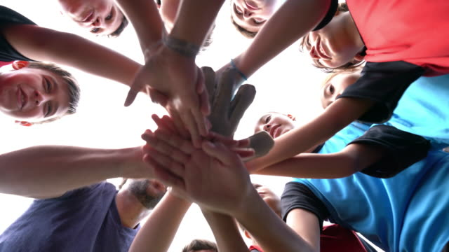 low angle view of kids football school team huddling together - childhood stock videos & royalty-free footage