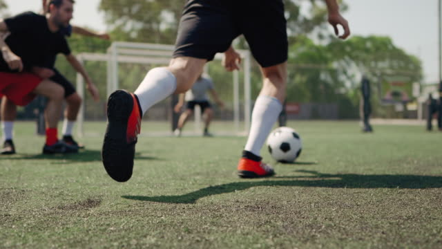 low angle view of male soccer player kicking soccer ball - football stock videos & royalty-free footage