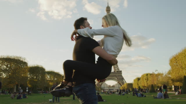 low angle view of man holding and spinning woman near eiffel tower / paris, ile de france, france - heterosexual couple stock videos & royalty-free footage