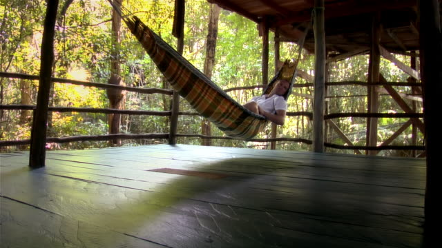 low angle view of man lying in hammock on deck / another man walking by in foreground/ the amazon, brazil - 仰向きに寝る点の映像素材/bロール