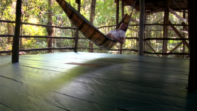 low angle view of man lying in hammock on deck / the amazon, brazil - hammock stock videos & royalty-free footage