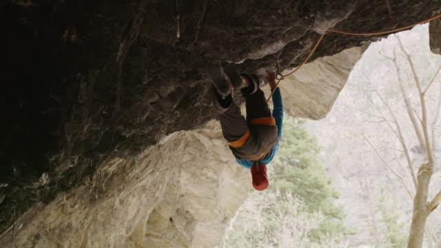 Low angle view of man rock climbing in cave / American Fork Canyon, Utah, United States
