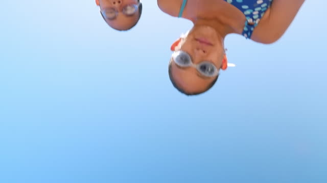 Low angle view of mixed race sisters dripping water after swimming