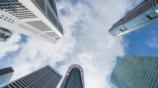 low angle view of modern building with moving cloud and blue sky, direct below shot time lapse video - river singapore stock videos & royalty-free footage