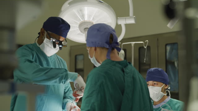 stockvideo's en b-roll-footage met low angle view of nurse handing forceps to surgeon with bloody gloves / salt lake city, utah, united states - chirurg