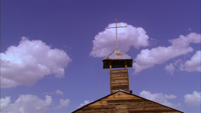 low angle view of old church steeple of rusty metal and aging wood, against a blue sky - steeple stock videos & royalty-free footage