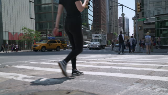 Low angle view of pedestrians and cyclists use the crosswalk at Columbus Circle in Manhattan, New York City