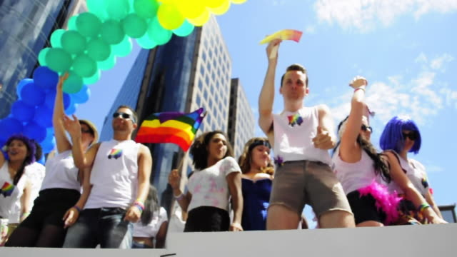 low angle view of people dancing on a float partaking on the toronto gay pride parade of the year 2013 the event is a tradition in the important... - festivalsflotte bildbanksvideor och videomaterial från bakom kulisserna