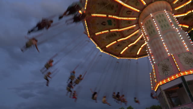 low angle view of people riding chain swing ride at amusement park / kaysville, utah, united states - 回転遊具点の映像素材/bロール