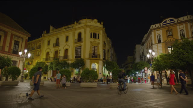 low angle view of people walking in plaza at night / seville, sevilla, spain - besichtigung stock-videos und b-roll-filmmaterial