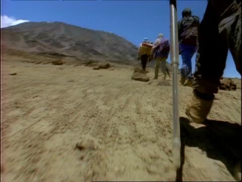 vidéos et rushes de ms low angle view of people's legs trekking toward mount kilimanjaro, tanzania, africa - endroit isolé