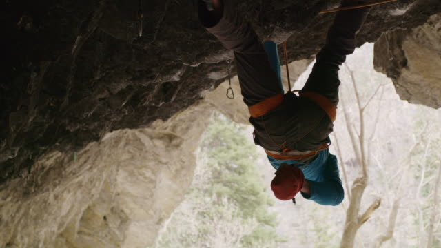 vídeos de stock, filmes e b-roll de low angle view of rock climbing man chalking hands / american fork canyon, utah, united states - gancho de alpinismo
