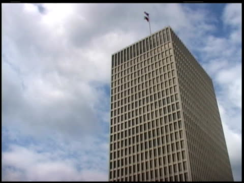 low angle view of skyscraper, flags flying from top; time lapse - fensterfront stock-videos und b-roll-filmmaterial