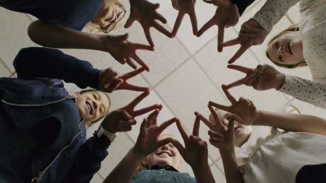Low angle view of smiling girls joining fingers in unity / Provo, Utah, United States