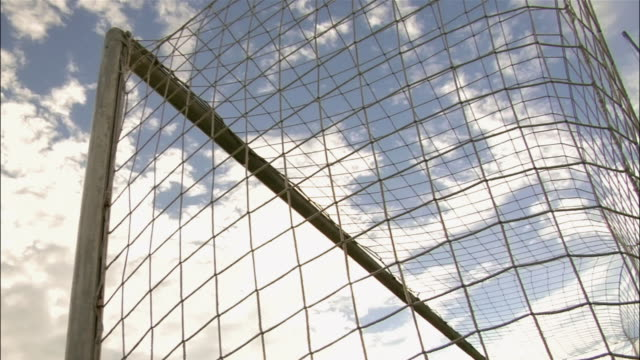 low angle view of soccer ball hitting back of net / hand of goalkeeper missing ball - netting stock videos & royalty-free footage