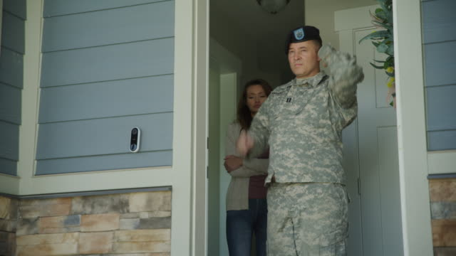 low angle view of soldier opening door to house then kissing wife and leaving / lehi, utah, united states - lehi stock videos & royalty-free footage