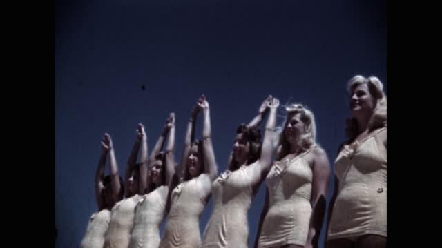vídeos de stock, filmes e b-roll de low angle view of synchronized swimming team with arms up against sky - de braço levantado