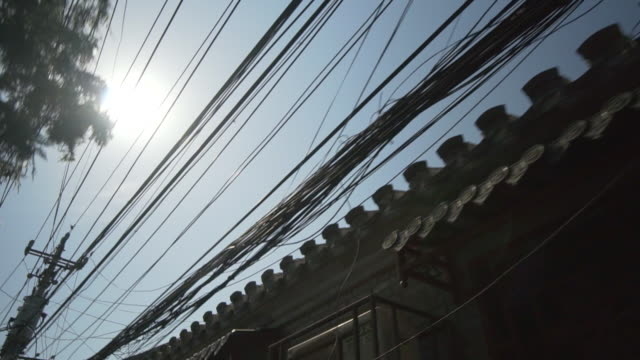 Low angle view of tangled power cables on electricity pylons by residential roofs - Beijing, China
