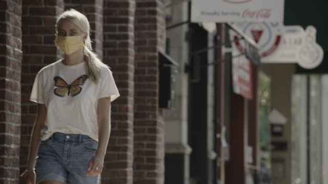 low angle view of teenage girl wearing protective mask walking on city sidewalk / provo, utah, united states - provo stock videos & royalty-free footage