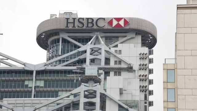 ws low angle view of the hsbc holdings plc headquarters building in standing against a gray sky cs hsbc logo displayed on top of the hsbc hq building... - bank of china tower hong kong bildbanksvideor och videomaterial från bakom kulisserna