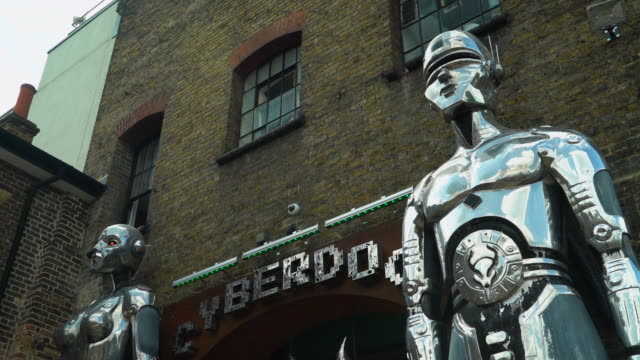 Low angle view of the metallic robots outside the entrance to Cyberdog in Camden Market, London