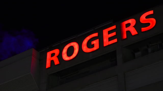 vídeos y material grabado en eventos de stock de low angle view of the rogers red sign located in the stadium of the same name the branding text contrasts with a blue illuminated steam coming out of... - identidad