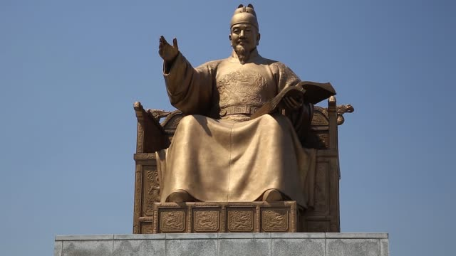 ms low angle view of the statue of king sejong the great stands at gwanghwamun square ms tourists take photographs at the square ws pedestrians cross... - general view stock videos & royalty-free footage