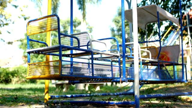 vídeos de stock e filmes b-roll de low angle view of train swing in playground park - equipamento de parque infantil