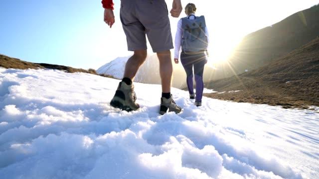 vidéos et rushes de vue d'angle faible de deux randonneurs marchant sur le sentier de montagne enneigée - alpes suisses