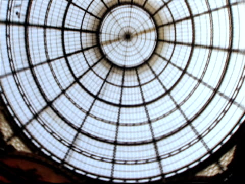 low angle view of vaulted glass ceiling of central dome of galleria vittorio emanuele ii / tilt down long shot pedestrians walking past prada store in arcade / milan, italy - galleria vittorio emanuele ii stock videos and b-roll footage