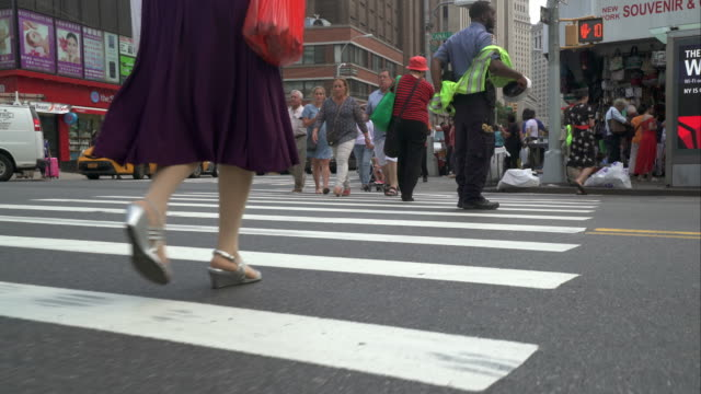 low angle view of woman in silver heels walks across busy new york city street. - eleganter schuh stock-videos und b-roll-filmmaterial