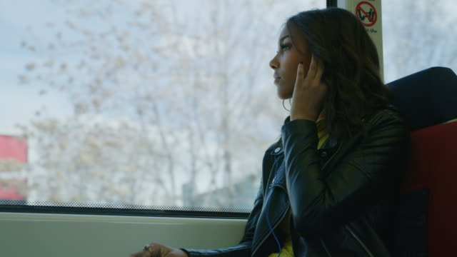 low angle view of woman passenger listening to earbuds on train / salt lake city, utah, united states - inserting stock videos & royalty-free footage