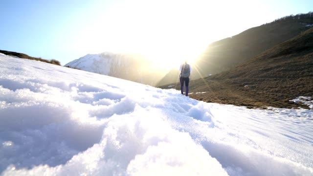 vídeos de stock, filmes e b-roll de vista de ângulo baixo dos pés da mulher caminhando na trilha de montanha de neve - tênis calçados esportivos
