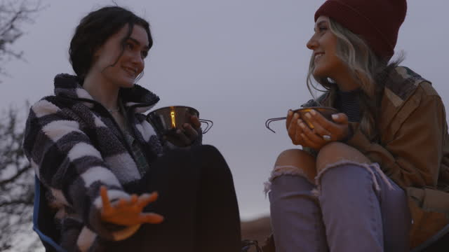 low angle view of women drinking and warming hands near campfire at dusk / moab, utah, united states - shaky stock videos & royalty-free footage
