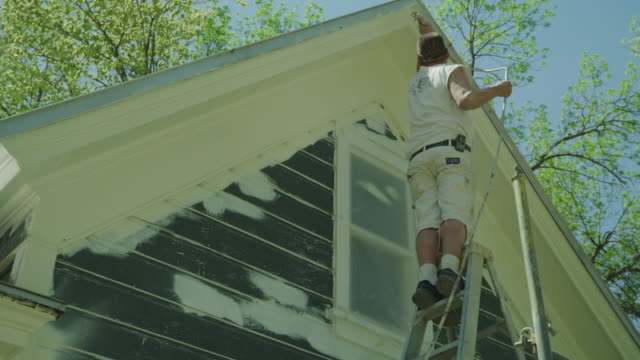 low angle view of worker painting roof of house / spring city, utah, united states - house painter stock videos and b-roll footage