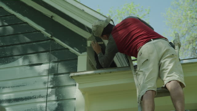 low angle view of worker painting roof of house / spring city, utah, united states - ladder stock videos and b-roll footage
