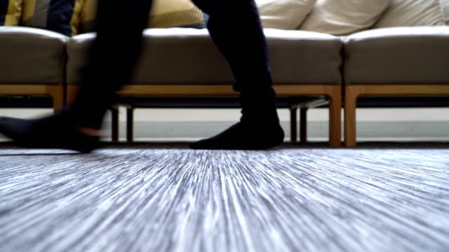 vídeos de stock e filmes b-roll de low angle view on the floor: people's feet with sock walking in domestic room - almofada roupa de cama