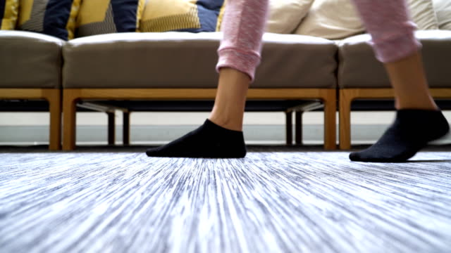 low angle view on the floor: woman's feet with sock walking in domestic room - sock stock videos & royalty-free footage