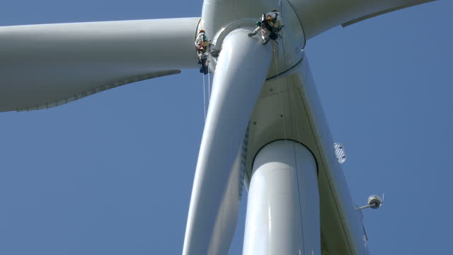 low angle view on wind-turbine and two rope access technicians - industrial climbers preparing for rappel (abseiling) down under hub around blade on the ropes, doing inspection, clear sky and sunny day. hub above them. sunny weather. - abseiling stock videos & royalty-free footage