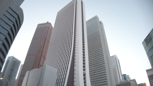 4k low angle view , panning ,tilt up , office building and sky in shinjuku - panning stock videos & royalty-free footage