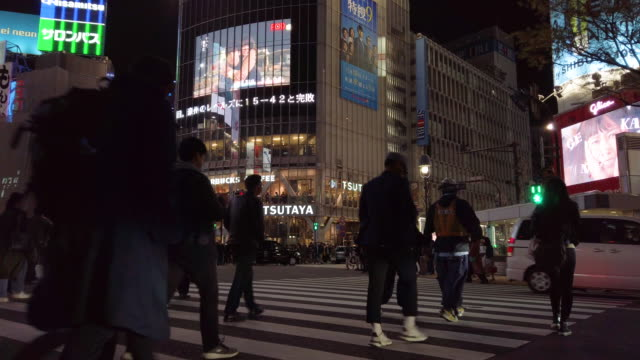 4k low angle view . pedestrians cross at shibuya crossing in tokyo , japan.4k low angle view . pedestrians cross at shibuya crossing in tokyo , japan. - tokyo japan stock videos & royalty-free footage