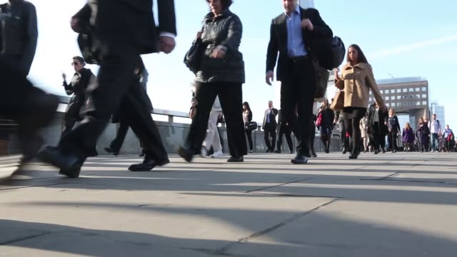 stockvideo's en b-roll-footage met low angle view pedestrians walk across london bridge with the shard tower standing in the background during the morning commute in london, u.k. ,... - adn