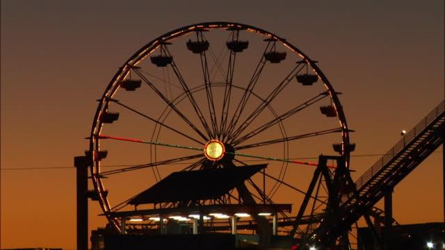 low angle view. silhouette of illuminated ferris wheel at santa monica pier. - santa monica pier stock videos & royalty-free footage
