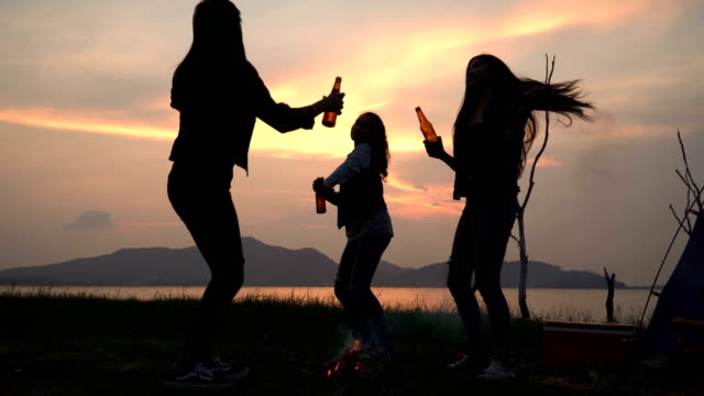 low angle view: silhouette of woman friends are drinking and dancing summer while having camping near lake at sunset - young women stock videos & royalty-free footage