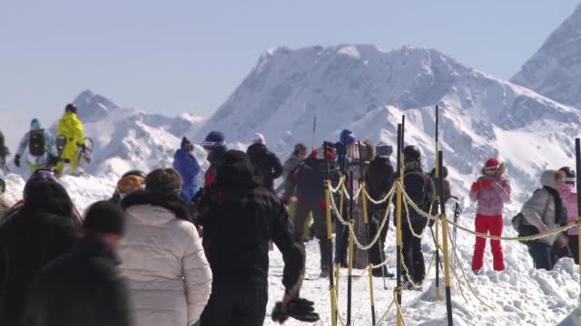 vídeos y material grabado en eventos de stock de low angle view skier towards and past down ski slope / skiers and snowboarders at top of slope / low angle views snowboarders and skiers setting off... - sochi