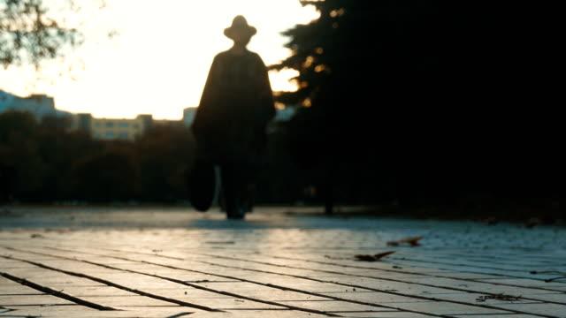 Tiro de cámara lenta vista de ángulo bajo de una femenina silueta caminando hacia cámara durante puesta del sol