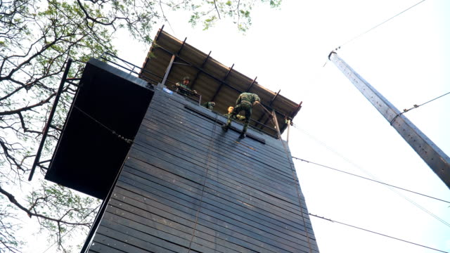 low angle view: soldier training rappel with rope by back down. military man does hanging on climbing equipment - abseiling stock videos & royalty-free footage