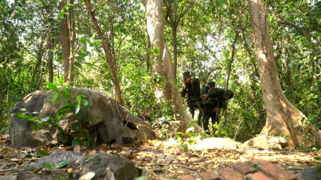 low angle view: Soldiers Carrying Injured his friend soldier in the tropical forest