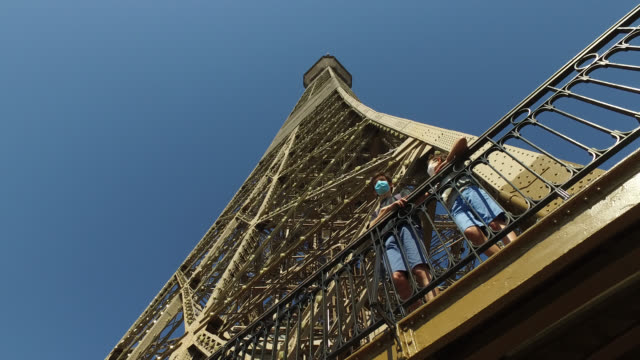 vídeos de stock, filmes e b-roll de low angle view. the eiffel tower reopens to the public on june 25, 2020 in paris, france. two children wearing facemasks gaze at the view on an... - torre eiffel